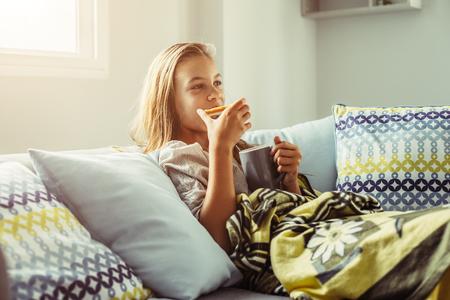 Muchacha pre adolescente de 10 años de edad envuelto en una manta que se relaja con el cacao y el desayuno en un sofá en la sala de estar. Cómoda fin mañana. Foto de archivo