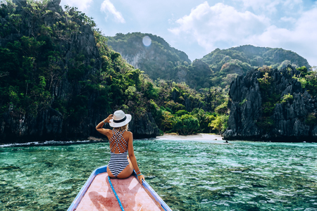 Back view of the young woman in hat relaxing on the boat and looking at the island. Travelling tour in Asia: El Nido, Palawan, Philippines. Stock Photo