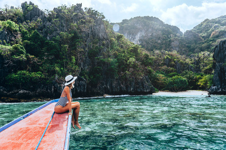 Back view of the young woman in hat relaxing on the boat and looking at the island. Travelling tour in Asia: El Nido, Palawan, Philippines. Standard-Bild