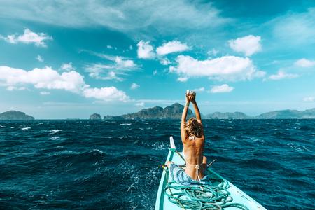 Achteraanzicht van de jonge vrouw die op de boot ontspant en naar het eiland kijkt. Reistocht in Azië: El Nido, Palawan, Filipijnen.