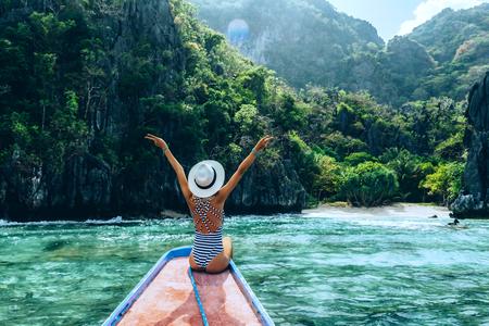 보트에 편안 하 게 하 고 섬 찾고 모자에 젊은 여자의보기를 백업합니다. 아시아 여행 : 엘니도, 팔라완, 필리핀. 스톡 콘텐츠