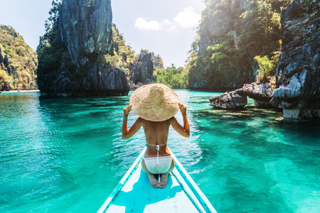 Back view of the young woman in straw hat relaxing on the boat and looking forward into lagoon. Travelling tour in Asia: El Nido, Palawan, Philippines. Standard-Bild