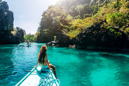 Back view of the young girl relaxing on the boat and looking at the island. Travelling tour in Asia: El Nido, Palawan, Philippines.