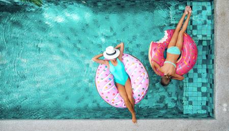 개인 빌라 수영장에서 도넛 LILO에 편안한 두 사람 (엄마와 아이). 여름 휴가 목가적. 위의 높은보기. 스톡 콘텐츠