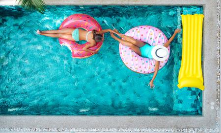 Twee mensen (moeder en kind) ontspannen op donut luchtmatras in het zwembad op particuliere villa. Opblaasbare ring en matras. Zomervakantie idyllisch. Hoge weergave van bovenaf. Stockfoto