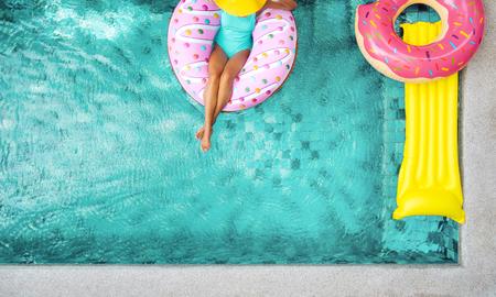 女性のプライベートのヴィラのプールサイドでドーナツ lilo でリラックス。インフレータブル、マットレス。牧歌的な夏の休日。上から高いビュー 写真素材