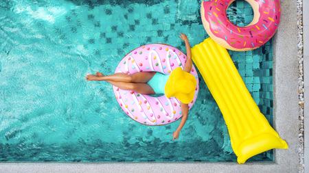 Vrouw ontspannen op donut luchtmatras in het zwembad op particuliere villa. Opblaasbare ring en matras. Zomervakantie idyllisch. Hoge weergave van bovenaf.
