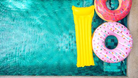 Donut lilo au bord de la piscine à la villa privée. Anneau gonflable et matelas. Vacances d'été idylliques. Haute vue par dessus. Banque d'images - 73168400