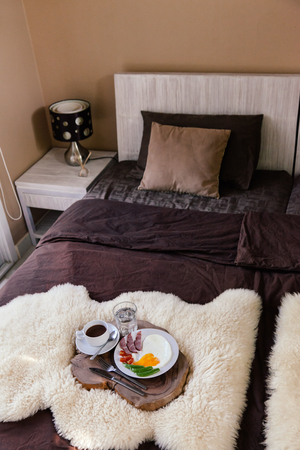 sheep skin: Breakfast on a wooden tray in hotel bedroom, brown linen, modern interior
