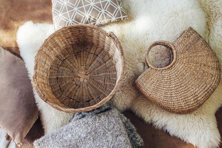 Lege rieten opbergmand en handtas, deken en kussens op schaap tapijt, bovenaanzicht van bovenaf. Natuurlijk en organisch interieur.