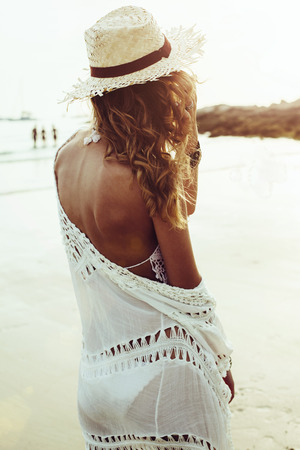 Beautiful boho styled model wearing white crochet swimsuit posing on the beach in sunlight Stock Photo