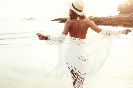 iluminado a contraluz: Hermosa modelo de estilo boho vestir de blanco posando ganchillo traje de baño en la playa de la luz del sol