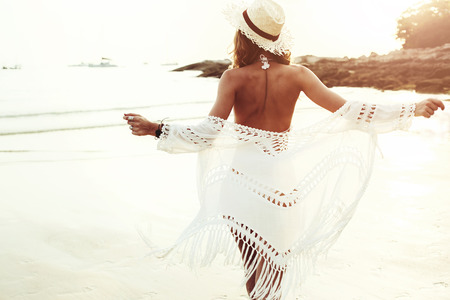 Beautiful boho styled model wearing white crochet swimsuit posing on the beach in sunlight Stockfoto