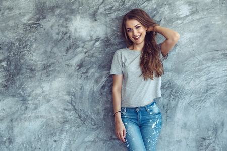 Young beautiful model wearing blank gray t-shirt and jeans posing against rough concgrete wall, minimalist street fashion style Stock Photo