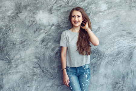 空白の灰色の t シャツとジーンズ大まかな concgrete 壁、シンプルなストリート ・ ファッション スタイルにポーズを身に着けている若い美しいモデル