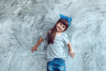 Fashion kind draagt een lege grijze t-shirt en spijkerbroek die tegen ruwe concrete muur staat, minimalistische straatmode kinderstijl Stockfoto