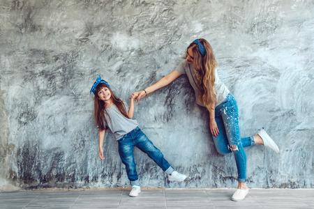 Mladá krásná máma s dcerou, která nosí prázdné šedé tričko a džíny, které představují proti hrubé kontrastní stěně, minimalistický styl módy v ulici, rodinný stejný vzhled, oblečení pro rodiče a dítě.
