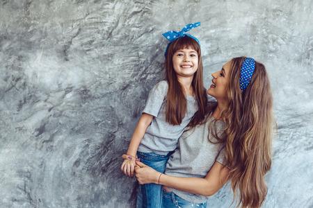 Hermosa joven madre con su hija en blanco que llevaba una camiseta gris y pantalones vaqueros posando contra la pared rugosa concgrete, estilo minimalista moda de la calle, la familia misma mirada, ropa para padres e hijos. Foto de archivo - 73348884