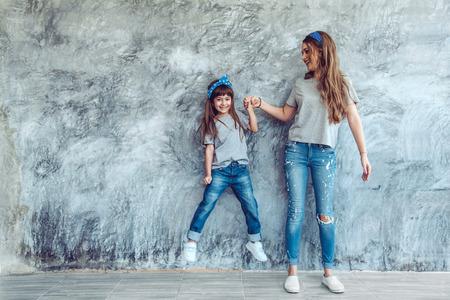 Hermosa joven madre con su hija en blanco que llevaba una camiseta gris y pantalones vaqueros posando contra la pared rugosa concgrete, estilo minimalista moda de la calle, la familia misma mirada, ropa para padres e hijos. Foto de archivo - 73348885
