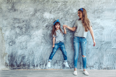 Young beautiful mom with her daughter wearing blank gray t-shirt and jeans posing against rough concgrete wall, minimalist street fashion style, family same look, clothing for parent and child. Reklamní fotografie - 73348885