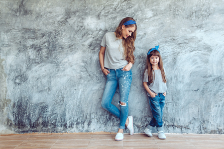 Jonge mooie moeder met haar dochter het dragen van leeg grijs t-shirt en jeans die tegen ruwe concgrete muur, minimalistische street fashion stijl, familie dezelfde look, kleding voor ouder en kind.