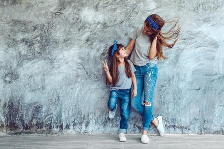 空白の灰色の t シャツとジーンズの大まかな concgrete 壁、シンプルなストリート ・ ファッション スタイル、家族に対してポーズを身に着けている彼女の娘と若い美しいお母さん同じ外観、親と子のための服します。 写真素材 - 73348917