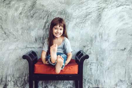 niño de manera que desgasta en blanco camiseta gris y pantalones vaqueros posando contra la pared concgrete áspera, calle minimalista estilo de los niños de la moda