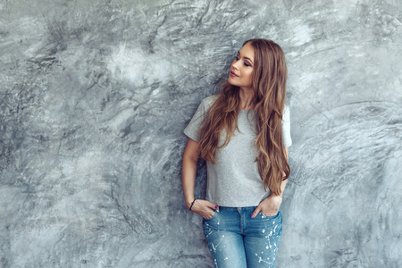 Young beautiful model wearing blank gray t-shirt and jeans posing against rough concgrete wall, minimalist street fashion style Standard-Bild