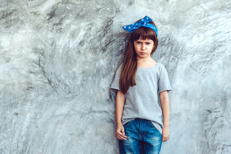 Fashion child wearing blank gray t-shirt and jeans posing against rough concgrete wall, minimalist street fashion kids style