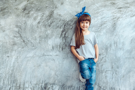 Fashion child wearing blank gray t-shirt and jeans posing against rough concgrete wall, minimalist street fashion kids style Stok Fotoğraf - 73348925