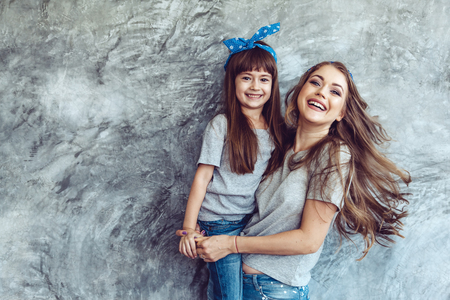 Молодая красивая мама с дочерью носить серую пустую футболку и джинсы, ставит против грубой concgrete стены, минималистского уличного стиля моды, семьи такого же внешний вида, одежды для родителей и ребенка.