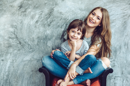 Young beautiful mom with her daughter wearing blank gray t-shirt and jeans posing against rough concgrete wall, minimalist street fashion style, family same look, clothing for parent and child.