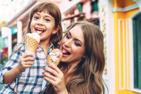 Maman avec ses 6 ans fille marchant le long de la rue de la ville et manger des glaces en face du café en plein air. De bonnes relations entre parents et enfants. moments heureux ensemble. Banque d'images - 73348928