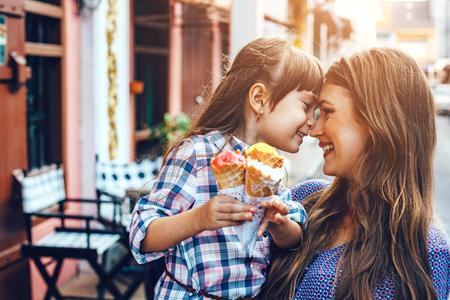 街を歩いていると屋外カフェの前にアイスクリームを食べる彼女の 6 歳の娘とママ。親と子の良好な関係。一緒に幸せな瞬間。 写真素材