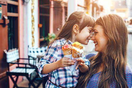 Mama met haar 6-jarige dochter die langs de stadstraat loopt en ijsje voor de openluchtcafe eet. Goede relaties tussen ouder en kind. Gelukkige momenten samen.