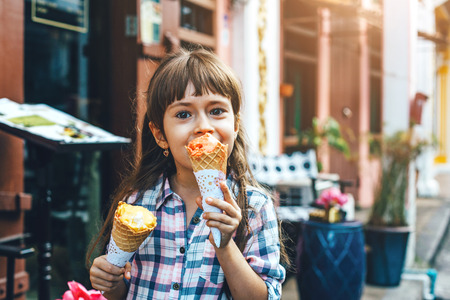 6 years old child walking along city street and eating ice cream in front of the outdoor cafe. Reklamní fotografie