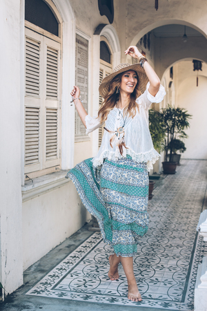 Fashion girl wearing bohemian clothing posing in the old city street. Boho chic fashion style.