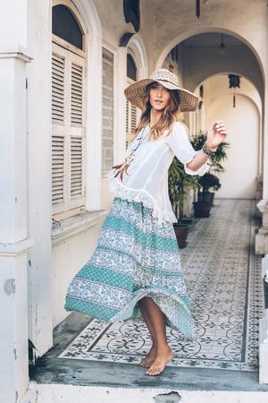 Fashion girl wearing bohemian clothing posing in the old city street. Boho chic fashion style.