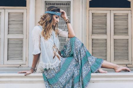 Mode meisje draagt boheemse kleding poseren in de oude stadsstraat. Boho chique mode stijl.
