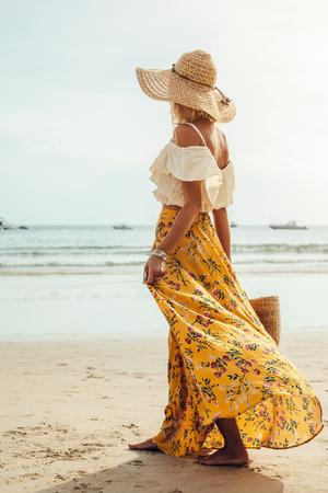 Girl wearing floral maxi skirt walking barefoot on the sea shore, Thailand, Phuket. Bohemian clothing style. 스톡 콘텐츠