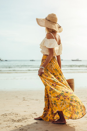 Girl wearing floral maxi skirt walking barefoot on the sea shore, Thailand, Phuket. Bohemian clothing style. Foto de archivo