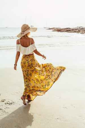 Girl wearing floral maxi skirt walking barefoot on the sea shore, Thailand, Phuket. Bohemian clothing style. Reklamní fotografie