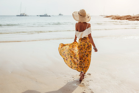 海の海岸は、タイ、プーケットで裸足で歩く花のマキシ スカートを着ている少女。自由奔放な服のスタイル。