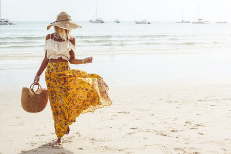 Girl wearing floral maxi skirt walking barefoot on the sea shore, Thailand, Phuket. Bohemian clothing style. Archivio Fotografico