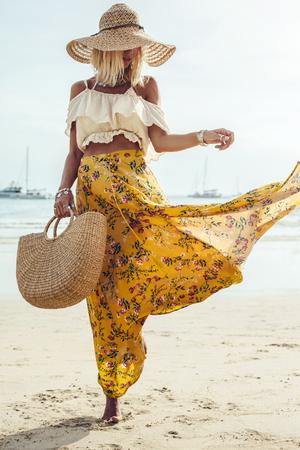 Meisje draagt bloemen maxi rok lopen op blote voeten op de kust, Thailand, Phuket. Boheemse kledingstijl.