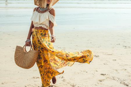 Girl wearing floral maxi skirt walking barefoot on the sea shore, Thailand, Phuket. Bohemian clothing style. Archivio Fotografico