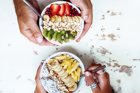 summer diet: Smoothie bowls with mixed tropical fresh fruits on wooden table with hands, top view from above. Summer healthy diet, vegan breakfast.