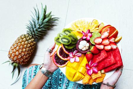両手は、上からの眺めをトップ フルーツ プレートを用意しています。エキゾチックな夏のダイエット。熱帯のビーチのライフ スタイル。