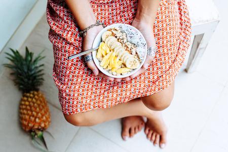 소녀 holdingin 손을 스무디 혼합 된 열 대 신선한 과일, 위에서 상위 뷰를 손에. 여름 건강한 식단, 완전 채식주의 아침.