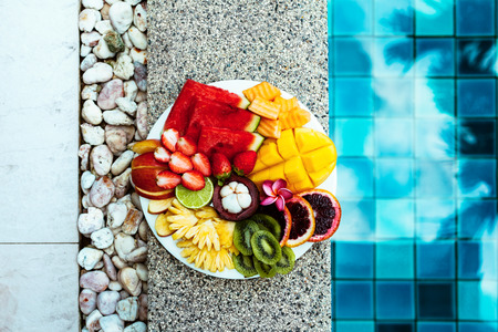 Fruit plate by hotel pool. Exotic summer diet. Tropical beach lifestyle.